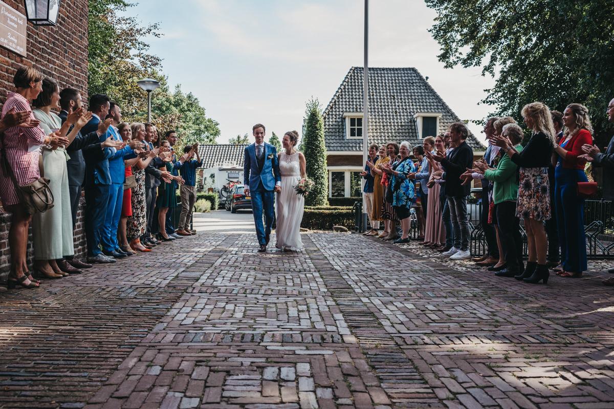 bruidspaar loopt door erehaag naar de ingang van de kerk