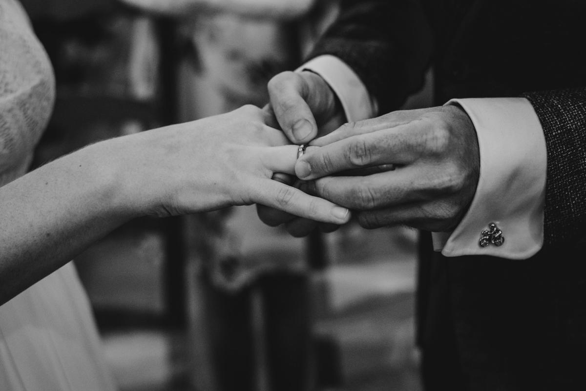 bruidegom doet de ring om de vinger van de bruid