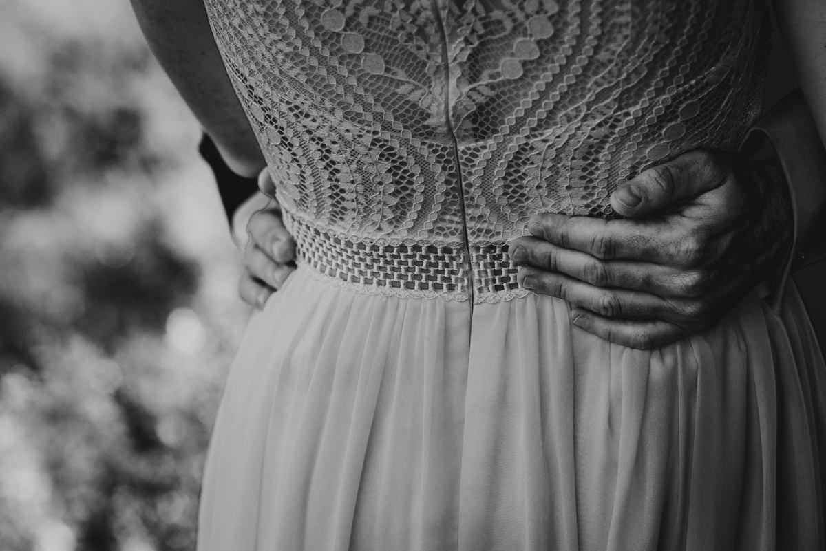 hand van de bruidegom op rug van de bruid
