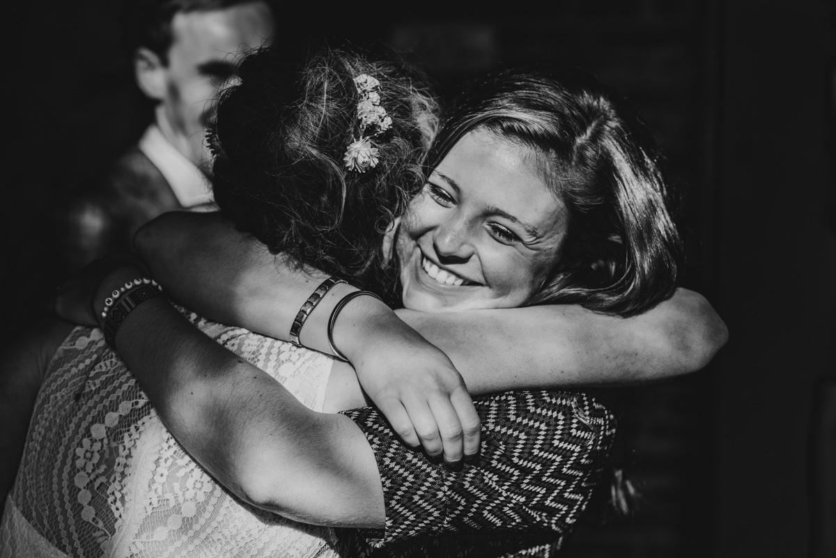 vriendin van de bruid omhelst haar na de kerkdienst